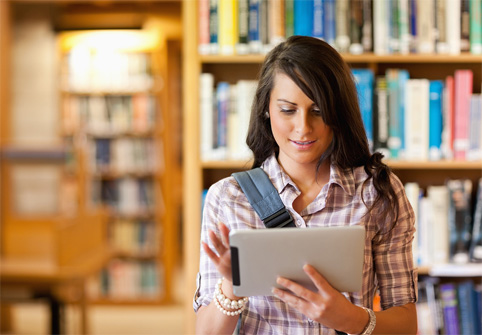 student-in-lbrary-referring-to-ipad-while-standing-with-backpack