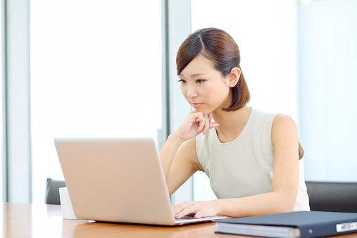 girl-with-short-hair-at-table-looking-at-laptop-with-pensive-expression